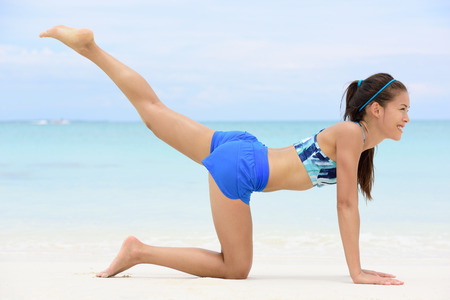 pilate: Kneeling leg lift butt toning exercise - Asian fitness woman working out on beach in blue sports bra and shorts strength training her glutes with pilates rear raised legs and donkey kick exercises. Stock Photo