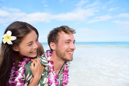 hawaiian lei: Beach couple having fun piggybacking and laughing on Hawaii travel holiday. Beautiful Asian mixed race woman piggybacking on Caucasian boyfriend wearing traditional Hawaiian lei on Oahu, Hawaii, USA.