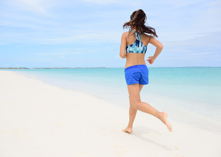 activewear: Runner training cardio running on beach. Back view of woman jogging barefoot in tropical destination barefoot in activewear blue sports bra and active shorts living a healthy life.