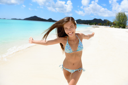 antigua: Beach bikini woman happy running with aspiration, joyful, free and playful on Jolly Beach, Antigua Girl on travel vacation holidays having fun. Asian Chinese Caucasian female model.