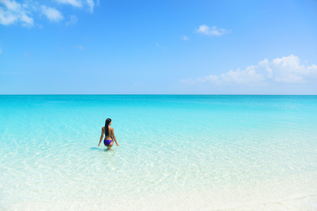 ビーチ休日人青い海洋を泳いでいます。セクシーなビキニ女性の完璧な青緑色の水と白い砂の楽園地でカリブ海で熱帯休暇を楽しんでリラックスで