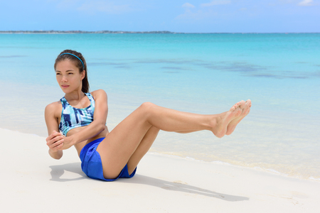 asian abs: Abs workout - fitness woman working out on beach doing russian twists exercises with raised legs to tone body and train oblique muscles. Stock Photo