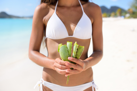 Aloe Vera - woman showing plant for skin care treatment using Aloes. Can be used as natural medicine or remedy against sunburn. Banco de Imagens - 47751059