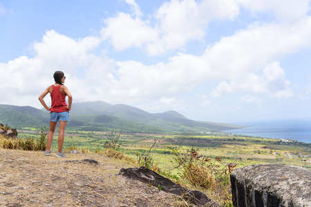 looking at: Hiking woman on travel excursion during holiday cruise looking at St Kitts and Nevis landscape. Caribbean nature during summer vacations. Young girl standing at lookout looking at viewpoint. Stock Photo
