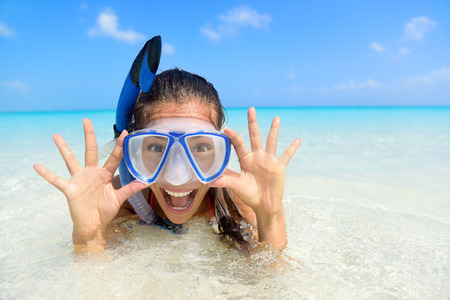 woman laying: Beach vacation fun woman wearing a snorkel scuba mask making a goofy face while swimming in ocean water. Closeup portrait of Asian girl on her travel holidays. Summer or winter destination.