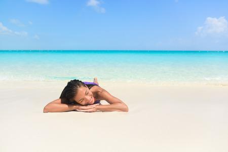 personas banandose: Mujer de relajación durmiendo vacaciones en la playa en la arena. Chica hermosa que se acuesta bajo el bronceado perfecto en el paraíso playa de arena blanca y prístina fondo azul marino.