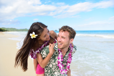 hawaiian lei: Beach couple having fun laughing on Hawaii holiday. Beautiful Asian mixed race woman piggybacking on Caucasian boyfriend wearing traditional Hawaiian lei on Oahu, Hawaii, USA.