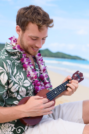 hawaiian lei: Man on beach playing ukulele instrument on Hawaii. Young man practicing on beach vacations in Hawaiian clothing wearing Aloha shirt dress and flower lei.