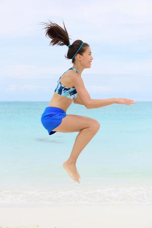 Crossfit remise en forme femme asiatique sur la plage faire squat jump exercices de pliométrie par saut et genoux touchantes dans le cadre d'une séance d'entraînement de base complet du corps et de style de vie actif.