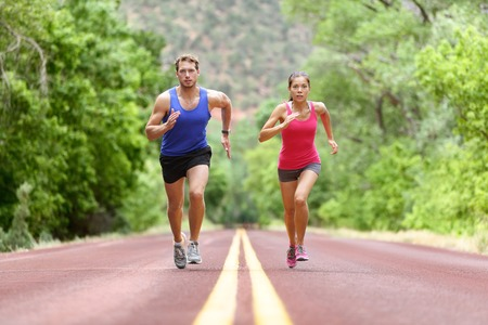 runners: Determined man and woman running on road against trees. Runners sprinting in Full length of sporty male and female are in sports clothing. Athletic runner fitness sport couple are exercising outside.