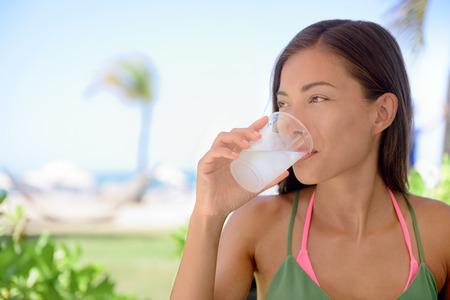 agua potable: Mujer joven que bebe el agua dulce o jugo de limón en la playa. Mujer está mirando a otro lado mientras se está sentado en el restaurante al aire libre. Turista hermoso es tener bebida saludable durante las vacaciones de verano.
