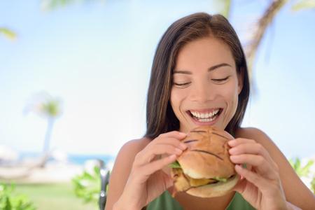 eten: Gelukkig vrouw die het eten van verse hamburger sandwich op het strand. Jonge vrouwelijke zit op outdoor restaurant. Mooie toeristische is met verse hamburger tijdens de zomervakantie vakantie. Stockfoto