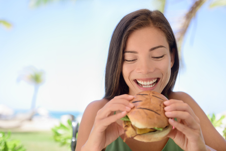 enjoying: Happy woman holding eating fresh burger sandwich at beach. Young female is sitting at outdoor restaurant. Beautiful tourist is having fresh burger during summer vacation holidays.