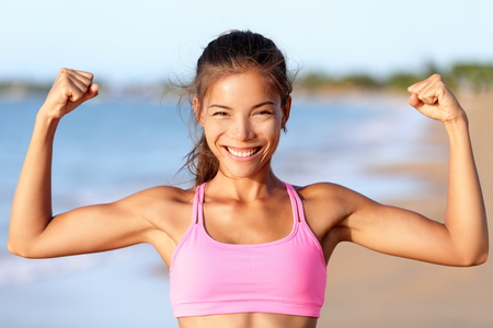 Happy sporty fitness woman flexing muscles on beach. Smiling young is wearing pink sports bra. Female is showing her strength and healthy lifestyle on sunny day.