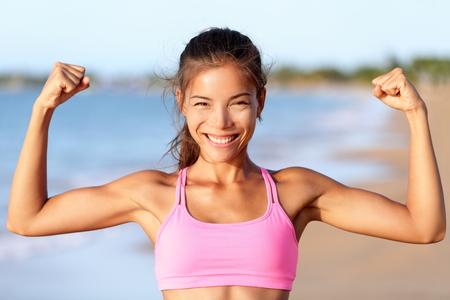 musculos: Mujer feliz de la aptitud deportiva flexionar los músculos en la playa. Sonriente joven está llevando sostén deportivo de color rosa. Mujer está mostrando su fuerza y ??estilo de vida saludable en el día soleado. Foto de archivo