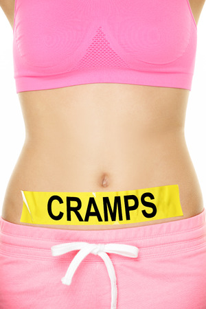 cramps: Midsection of woman with cramps sign stuck on stomach. Young female is representing stomach ache concept. Woman is wearing pink sports bra. She is isolated over white background. Stock Photo