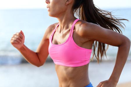 L'avancement déterminée Sprint Woman Runner Sur la plage. Médiane de la formation de la femme sportive sur la plage. Jeune femme porte rose soutien-gorge de sport. Coureur déterminé exerce sur la journée ensoleillée.