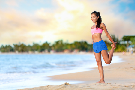 girl bra: Happy young woman doing stretching exercise on beach. Smiling female is wearing sports bra and shorts. Full length of sporty woman looking away while exercising on sea shore against cloudy sky. Stock Photo