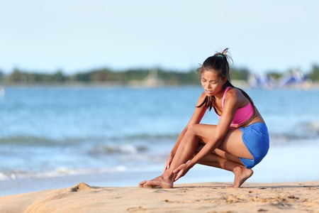 Young jogger running suffering from ankle pain injury on beach. Full length of female runner in sportswear. Woman is holding her twisted leg while crouching on sea shore. Zdjęcie Seryjne - 47751311