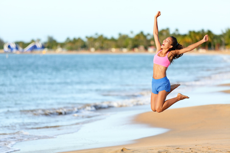 midair: Excited woman jumping at beach. Cheerful female in sportswear is enjoying on shore. Runner with arms raised screaming in midair on sunny day. Stock Photo