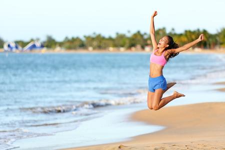mujeres felices: Mujer emocionada que salta en la playa. Femenino alegre en ropa deportiva está disfrutando en la orilla. Runner con los brazos levantados gritando en el aire en un día soleado. Foto de archivo