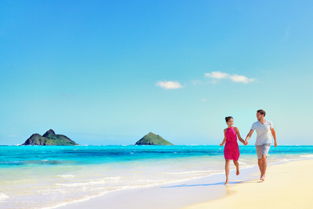 romance: Hawaii casal de f�rias andando a relaxar na areia branca e �gua azul-turquesa do oceano intocada na praia havaiana Lanikai, ilha Oahu, EUA. Fundo do feriado com c�u azul c�pia-espa�o para o conceito de viagem.