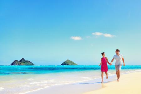 parejas jovenes: Hawaii pareja de vacaciones walking relajarse en la arena blanca y agua turquesa del oc�ano pr�stino en la playa de Hawai Lanikai, la isla de Oahu, EE.UU.. Vacaciones de fondo con azul cielo copia espacio para el concepto de viaje. Foto de archivo
