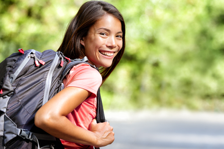 backpack: Happy young Asian Chinese backpack girl student. Cute adult woman backpacker smiling at camera with school bag doing summer backpacking travel in nature. Stock Photo