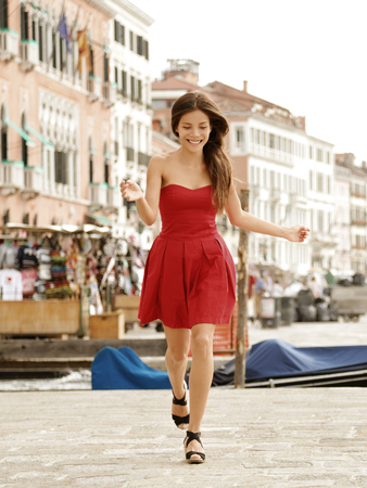 strapless dress: Venice happy woman in fashion red dress. Romantic scene in Italy, of a beautiful Asian female model wearing italian fashionable gown in summer vacation travel destination.