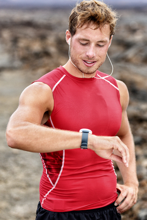 cardio workout: Runner looking at his heart rate monitor, activity tracker smartwatch. Active athlete looking at his smart watch using app after cardio workout for pace and distance information. Stock Photo