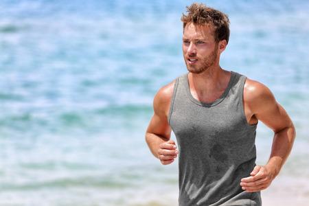 sudando: Sudoración activa corredor corriendo en la playa. Apuesto joven atleta masculino que desgasta la tapa del tanque gris para absorción del sudor durante cardio intenso trabajo el día de verano caliente con el fondo del océano.