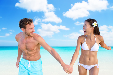 Beach vacation fun couple in bikini swimwear and blue swim shorts on perfect turquoise ocean background. Happy people holding hands laughing with slim shape. Weight loss suntan body care concept.