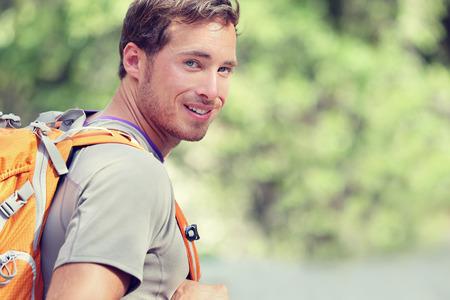 Jonge glimlachende rugzak man in de zomer bos natuur. Gelukkig knappe mannelijke volwassene student op zoek naar camera lopen wandelen in het bos achtergrond. Schooltas of reizen backpacken concept. Stockfoto