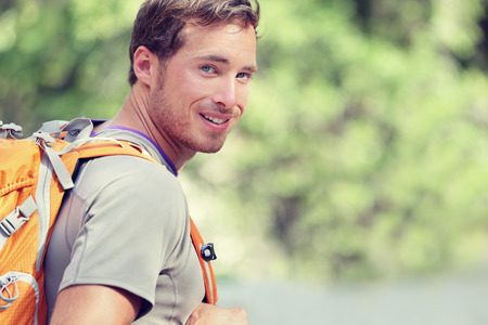 backpack: Young smiling backpack man in summer forest nature. Happy handsome male adult student looking at camera walking hiking in forest background. School bag or backpacking travel concept.