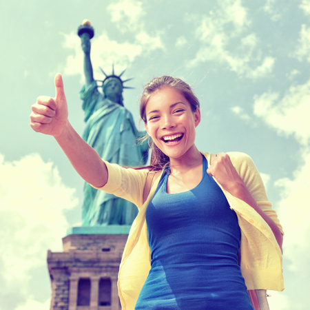 chinese american ethnicity: Happy Asian Chinese tourist doing thumbs up having fun visiting the Statue of Liberty, american landmark in New York City. Famous touristic attraction, USA.