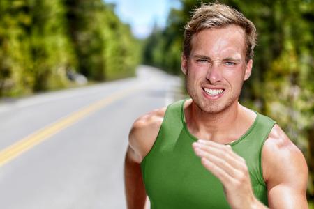Sportowiec na intensywnym treningu kardio biegu. Portret mężczyzny sprintera lub dużego biegacza odległość w ciężkim treningu wytrzymałościowego na górskiej drodze w charakter letnich. Ustalenie, ostrość pojęcia. Zdjęcie Seryjne