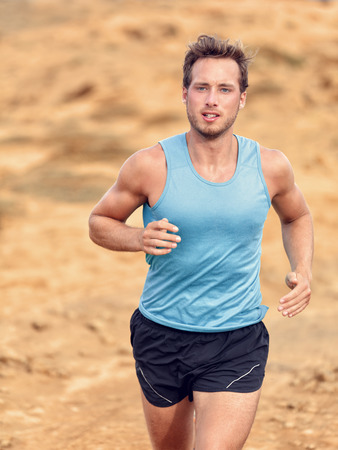 male athlete: Trail runner training cardio running on rocky mountains yellow sand path in nature. Caucasian male athlete waist up portrait jogging living an active healthy lifestyle exercising outdoors.