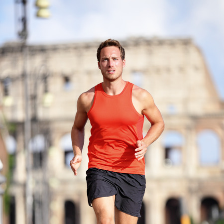 man exercise: Runner man running at italian city Rome marathon near Colosseum, Roma, Italy. Handsome male athlete training cardio jogging on street with famous touristic attraction landmark in the background. Stock Photo