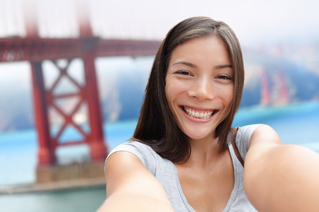 san: Selfie girl on San Francisco Golden bridge travel. Cute young Asian woman adult taking picture with her smartphone during summer vacation in front of the famous American attraction, California, USA.