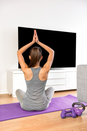 meditation room: Yoga girl doing meditation exercise in living room at home. Woman watching fitness dvd workouts or streaming online videos on smart tv with flat screen television doing a training program.
