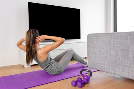 apartment: Home fitness concept. Woman doing strength training abs situps bodyweight floor exercises watching a dvd workout or web videos on a smart tv in the living room of a house or apartment. Stock Photo