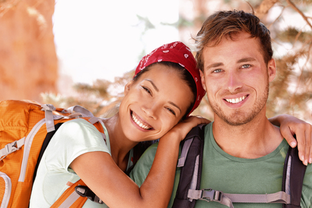 rucksacks: Happy young hikers backpacking on summer travel. Portrait of two friends teenagers or student couple wearing rucksacks bags smiling hiking during road trip vacation or doing volunteering.