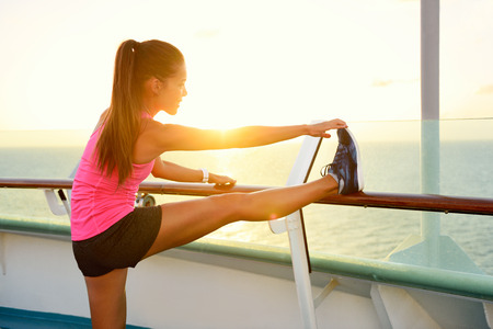 stretching: Muchacha de la aptitud que estira la pierna en vacaciones en crucero. mujer adulta joven que hace estiramientos después de correr sesión de ejercicios en la puesta del sol en el balcón de un buque de crucero durante las vacaciones de verano. Estilo de vida activo.