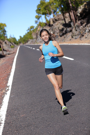 sports wear: Female road runner training running in outdoor nature. Asian woman jogging fast working out her cardio in blue top and black shorts activewear. Stock Photo