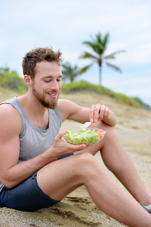 takeout: Healthy fit man on vegan diet eating organic food on beach. Muscular young fitness guy after exercise eating take-out food of prepared fresh salad and veggies.