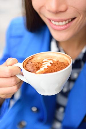 capuchino: Latte arte del café primer taza mano. Cosecha de la mujer que sostiene una taza de la bebida para el desayuno o romper un capuchino con un dibujo de forma Rosetta en la espuma hecha por un barista. cafetería Europea.