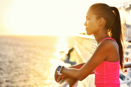 resting heart rate: Active woman relaxing after run on cruise ship looking at the sea during summer holidays. Asian runner girl wearing smartwatch heart rate activity monitor living a healthy lifestyle.