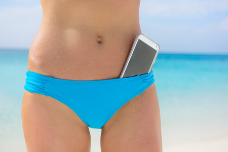 blue button: Beach woman bikini bottom. Lower body crop with smartphone screen in focus. Mobile phone in swimwear bathing suit for weight loss, fitness, fashion, summer, 4g app, or vacation concept.