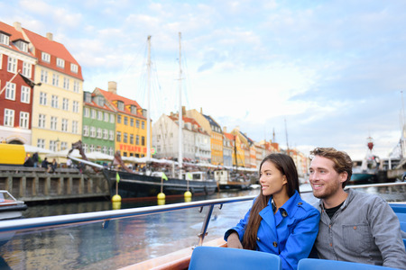 Copenhagen tourists people on cruise boat tour on water canal in old port Nyhavn. Young multiracial couple visiting famous European destination in Europe during fall or spring.