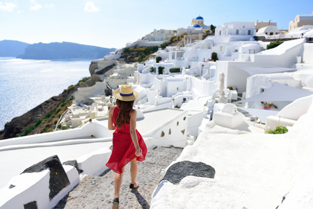 mediterranea: Santorini travel tourist woman on vacation in Oia walking on stairs. Person in red dress visiting the famous white village with the mediterranea sea and blue domes. Europe summer destination.